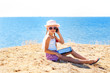 girl on the beach with laptop and phone