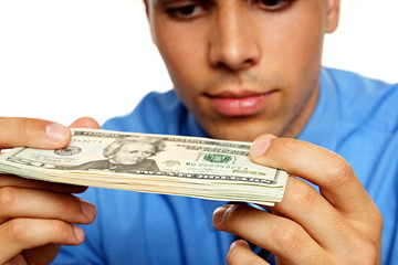 Thoughtful young man in blue shirt looking at banknotes