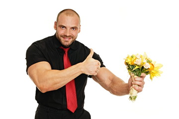 Man in black shirt shows on bouquet of flowers