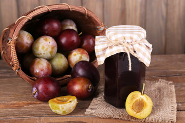 Tasty plum jam in jar and plums