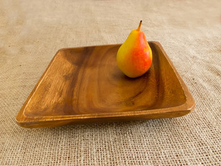 Pear on wooden plate