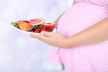 Young pregnant woman holding plate with fruits