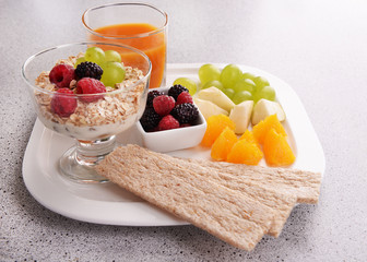 Slices of fruits with berries and muesli on table close up