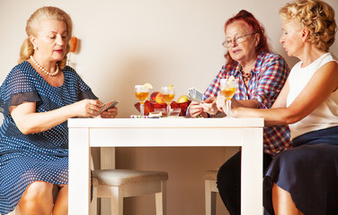 Senior women chatting and playing cards, at living room