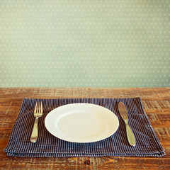 White plate on tablecloth over vinatge background