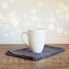 Coffee cup on vintage table over bokeh background
