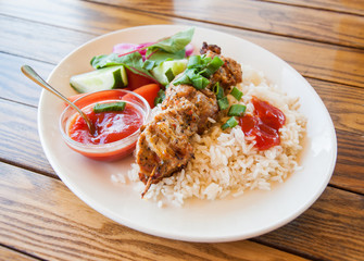 Plate with kebab and rice on wooden background