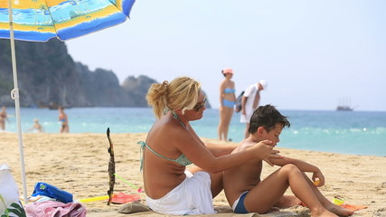 mother applying sunscreen to son on the beach at summertime