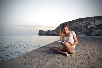 young beautiful girl who is reading a book on a pier