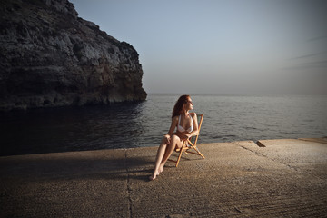 young beautiful woman who is sitting on a pier