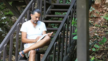 attractive middle age man reading a book on the stairs