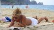 attractive blonde women reading a book on the beach
