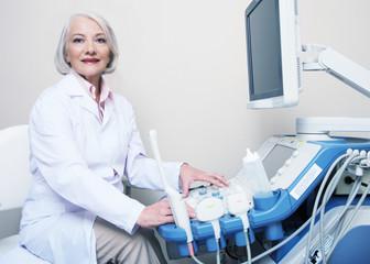 Senior female doctor smiling while setting up ultrasound machine