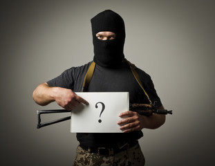 Gunman is holding white paper with question-mark.