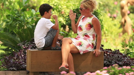 mother and son playing rock paper scissors in the park