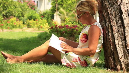 blonde women reading a book in the park