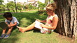 mother reading book and son playing digital tablet in the park