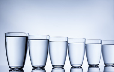 column glasses of water on white background