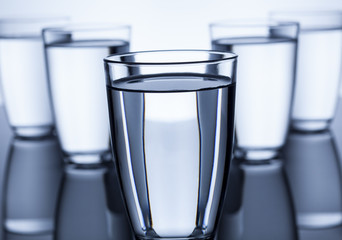 group of glasses filled with water on white background