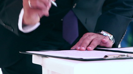 Businessman/diplomat/groom in elegant suit signing a document