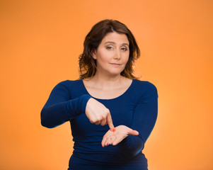 Woman gesturing pay me my money back, orange background