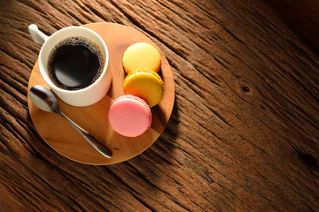 A cup of coffee and pastries(macaron) on old wooden table