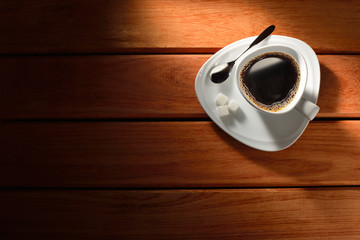 A cup of coffee and sugar cute on wooden table
