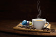 Cup of coffee with coffee beans and pastries on wooden table