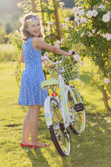 Cycling -  girl with bicycle in summer garden