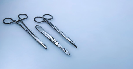 Three surgical instruments on blue.gray background