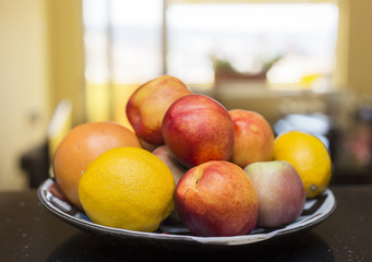 Assortment of juicy fruits in plate, on bright background