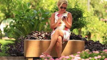 attractive blonde women using smartphone in park