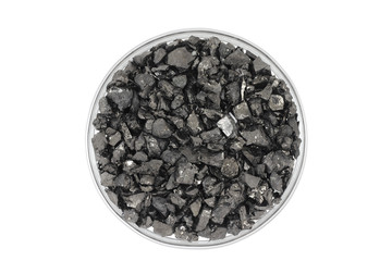 crushed coal in a glass on a white background