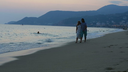 happy couple walking on the beach together at sunset