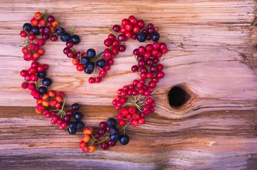 heart from various berries on wooden background