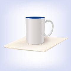 White ceramic cup standing on a napkin.