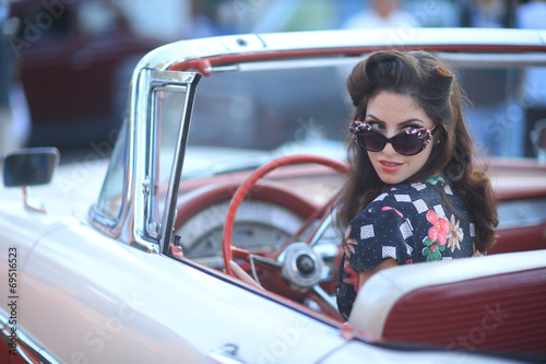 Lovely Woman Posing and and Around a Vintage Car - 69516523