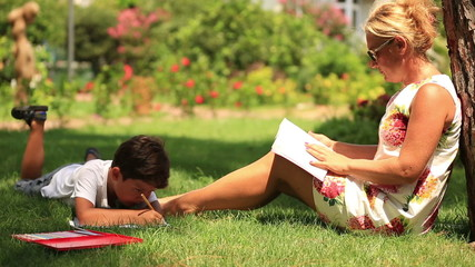 Child  painting,  mother reading a book in the park