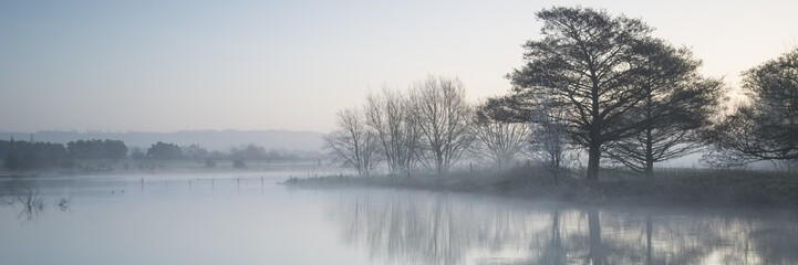 Panorama landscape of lake in mist with sun glow at sunrise