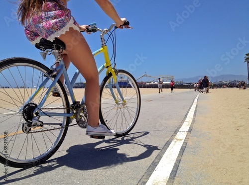 Pretty Woman riding a bicycle along Santa Monica Beach pathway