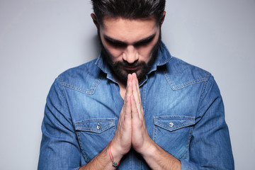 Man in blue shirt praying