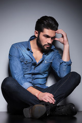Man in blue shirt thinking