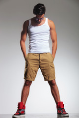 man with hands in his pockets looking down