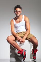 man in undershirt sitting on a cube
