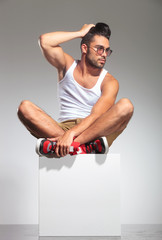 man in yoga position on  cube with hand on head