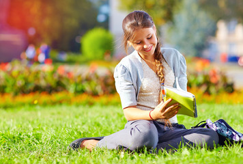 cute girl with notebook sitting in colorful park