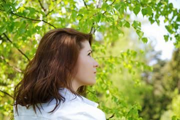 The girl looks upwards among green foliage