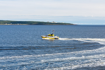 Yellow Pilot Boat Cutting Across Bay