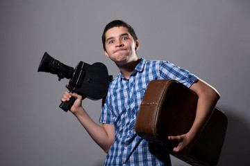 Portrait of a young cameraman with old movie camera and a suitca