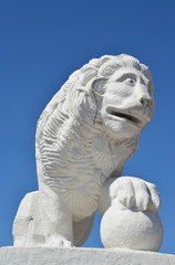 White stone lion with a sphere against the blue sky. St. Petersb